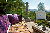 A villa terrace, Bench furnished with pillows, overlooking the mountain landscape in Andalucia