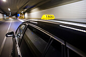 Taxicab with the roof light illuminated, driving at high speed through a tunnel