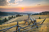Sunset over the mountains and valleys of Montana, Strong wooden stock fencing on grasslands