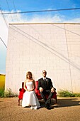 Newlyweds Sitting Outdoors In Urban Setting