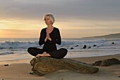 Mature Woman In Yoga Position On Seashore At Sunset