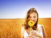 Young Woman Smelling Flower In Field