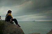 A Boy Sits On A Rock Watching The Ocean