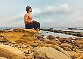 A Man Sitting In A Meditation Pose On A Rock Formation In Parque Natural Del Estrecho, Tarifa, Cadiz, Andalusia, Spain