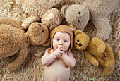 Baby Wearing Bear Cap Surrounded By Teddy Bears
