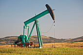 Pumpjack In A Field In The Foothills At Sunrise With Blue Sky, Longview Alberta Canada