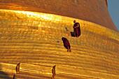 Two monks next to the golden wall of the Shwedagon Pagoda, Yangon, Myanmar, Burma, Asia