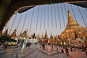 Viw of the Shwedagon Pagoda with people on the square, Yangon, Myanmar, Burma, Asia
