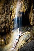 Woman enjoying a shower beneath a waterfall, Caribbean