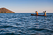 Two boys paddling in a dugout, a wooden canoe on Lake Malawi, Malawi, Africa