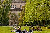 Young people relaxing on a park lawn, State theatre in the background, Brunswick, Lower Saxony, Germany
