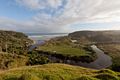 Farmland on the Anatori River estuary, pastures surrounded by arm of the river and coastline, west coast of South Island, New Zealand