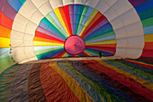 Brightly coloured hot air balloon from the inside, about to be filled with air before take-off, Sport
