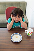 Young Maori girl leaning on the table in front of an empty plate, North Island, New Zealand