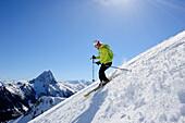 Female backcountry skier downhill skiing from mount Brechhorn, Grosser Rettenstein in background, Brechhorn, Kitzbuehel Alps, Tyrol, Austria