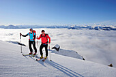 Two backcountry skiers ascending to notch Rote-Rinn-Scharte, hut Gruttenhuette in background, Kaiser-Express, Rote-Rinn-Scharte, Wilder Kaiser, Kaiser mountain range, Tyrol, Austria