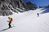 Man and woman downhill skiing from Rote-Rinn-Scharte to cirque Hoher Winkel, Kaiser-Express, Wilder Kaiser, Kaiser mountain range, Tyrol, Austria
