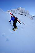 Young man descending gully Egersgrinn on crampons, Pyramidenspitze, Kaiser Express, Zahmer Kaiser, Kaiser mountain range, Tyrol, Austria
