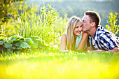 Young couple lying on grass, man kissing woman, Styria, Austria