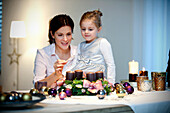 Mother and daughter (4 years) lighting candle on an Advent wreath