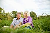 Senior couple sitting on grass, Vienna, Austria
