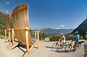 Giant chairs, view from Algund towards Meran, Couple on electric bikes, E-bikes, South Tyrol, Italy