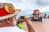 Tourists and local tourist guide at the Southernmost Point Landmark, Key West, Florida, USA