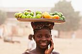 Girl carrying fruits on her head, Segou, Mali