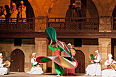 Whirling dervish performing a Sufi dance at the Al-Ghouri Mausoleum at night, Cairo, Al Qahirah, Egypt