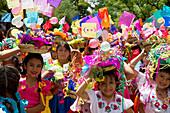 Girls carrying festive baskets in the Entrada de Comadritas parade during the Carnaval Chapaco, Tarija, Bolivia