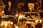 Skeletons (calacas) decorate this grave during the celebration of Día de los Muertos, the Day of the Dead at the Tzurumútaro cemetery. People decorate the graves of their loved ones with offerings of flowers, particularly marigolds (cempoalxóchitl or z