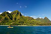 Hawaii, Kauai, Na Pali Coast, Kayaker paddling along coastline, Beautiful mountains in background. Editorial Use Only.