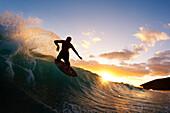 Hawaii, Maui, Makena - Big Beach, Skimboarder carving wave, Sunset light.