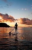 Hawaii, Kauai, Woman stand up paddling in ocean, Beautiful sunset.