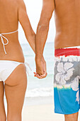 Hawaii, Couple holding hands on beach, Close-up of midriff, View from behind.