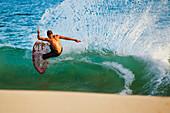 Hawaii, Maui, Makena, Skimboarder carves big turn on wave