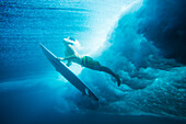 Indonesia, Bali, Surfer duck dives under wave, view from underwater