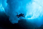 Hawaii, Lanai, Scuba diver under billowing surf breaking over reef.