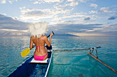 French Polynesia, Moorea, Woman paddling in ocean in outrigger canoe.