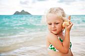 Hawaii, Oahu, Lanikai, Young girl listening to a shell.