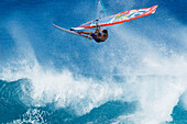 Hawaii, Maui, Ho'okipa, Professional windsurfer Ricardo Campello catches big air off wave. FOR EDITORIAL USE ONLY.