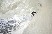 California, Ventura, Surfer in the barrel on foamy ocean wave. FOR EDITORIAL USE ONLY.