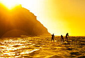 Hawaii, Oahu, Portlock, Three Stand Up Paddlers passing Spitting Caves at sunrise.
