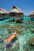 French Polynesia, Moorea, Woman sunbathing on inflatable raft over ocean reef, Luxury resort bungalows over ocean.