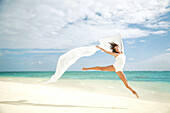 Hawaii, Oahu, Lanikai Beach, Beautiful female ballet dancer leaping into air on beach with white flowing fabric.