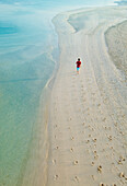 United Arab Emirates, Dubai, Man walking on beach next to Burj Al Arab hotel, View from above.