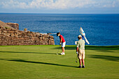 Hawaii, Lanai, Couple putting on the green at The Challenge at Manele golf course.