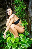 Hawaii, Kauai, Haena Falls, Attractive young woman on near the falls.