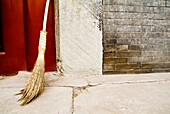 China, Beijing, A broom leaning against a cement wall, common street scene.