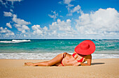 Hawaii, Woman sitting on the beach at a remote tropical location.